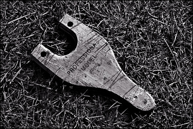 A child's wooden toy slingshot in the grass in the backyard of an abandoned house. The label on the slingshot says that is a professional model.