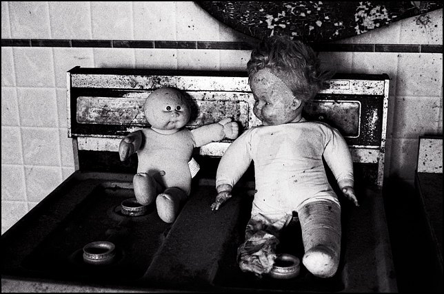 A Cabbage Patch Kid and another broken doll sit together on the rusty stove in the trashed kitchen of an abandoned house.