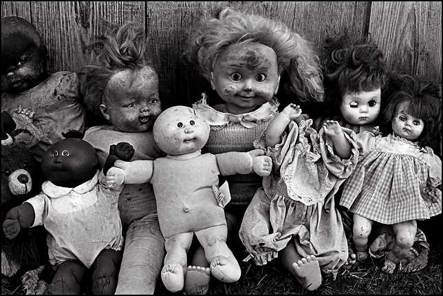 Nine old broken dolls sit together next to a weathered wood barn. There are two Cabbage Patch Kids, a Cricket talking doll, a teddy bear, a headless doll, and a couple of baby dolls.