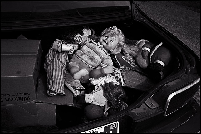 Several old broken dolls in the trunk of a car. There is a Cricket Doll, a Cabbage Patch Kid, and a Santa Claus doll.