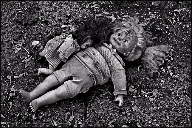 A Cricket talking doll hugs a sleeping baby doll on the ground where an abandoned house once stood.