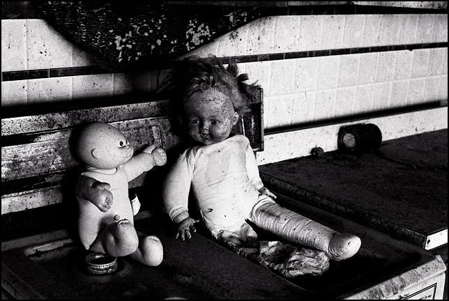Two old dolls sit on the stove in an abandoned house.
