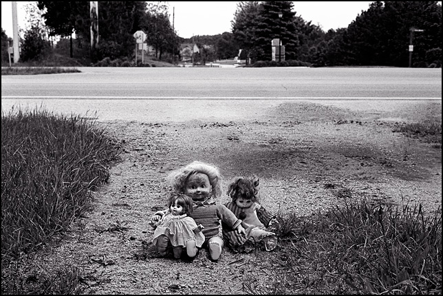 Three old dolls sit on the driveway of the abandoned house where they were found.