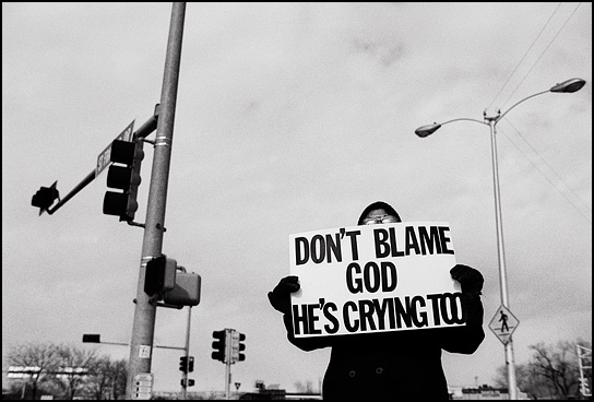A peace activist protesting the war in Iraq holds a sign that says Dont blame God, He's crying too.
