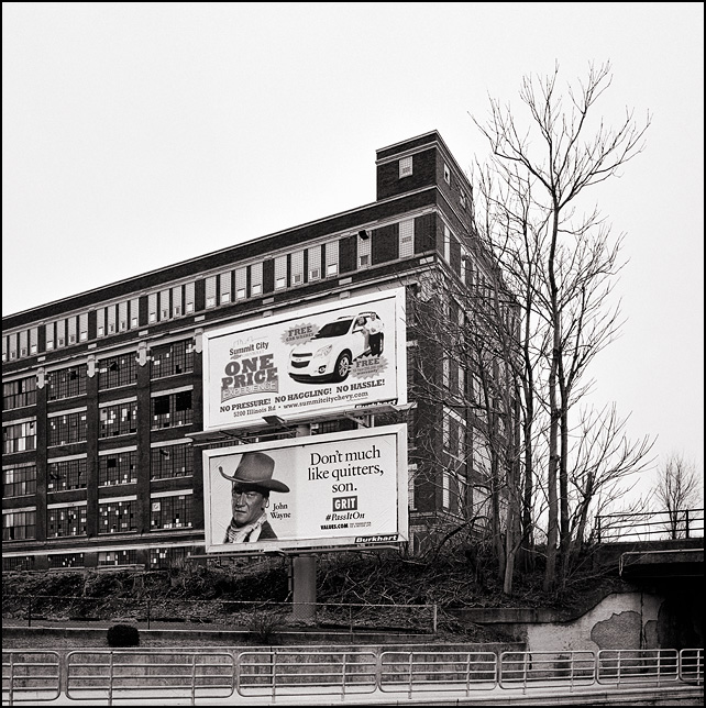 A billboard with a quote from John Wayne stands in front of one of the abandoned General Electric factory buildings on Broadway in Fort Wayne, Indiana. The sign says, Don't Much Like Quitters, Son.