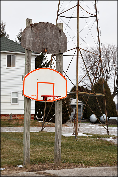 Two basketball backboards, one above the other, next to a farmhouse on State Road 37, near the state line, in rural northeast Allen County, Indiana. One of the backboards is an old one of weathered wood, and the hoop is missing. The other is a modern one with a hoop.