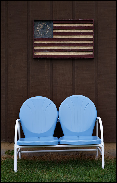 A blue two-seat metal motel chair bench sits under a rustic wooden folk-art American flag on the side of a garage behind a house in the small town of Willshire, Ohio.