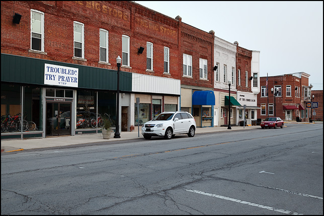 A block of old brick storefronts in the small town of Warren, Indiana. One building has a sign over the door telling people to solve their troubles by Prayer.