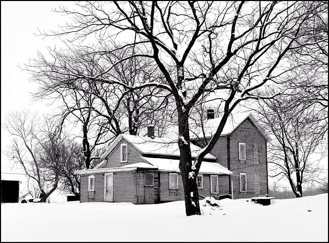 An abandoned farmhouse in a snow covered landscape on Maysville Road near Fort Wayne, Indiana.