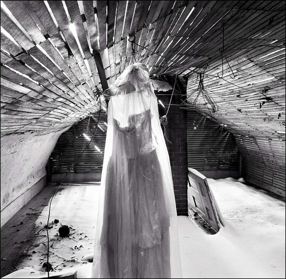 An old white wedding dress hanging in the attic of an abandoned farmhouse. The roof is partly gone and the floor is covered in snow.