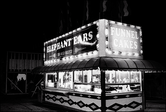 The brightly lit Elephant Ear concession stand at a carnival glows in the dark night. The carny inside is looking out the window at me.