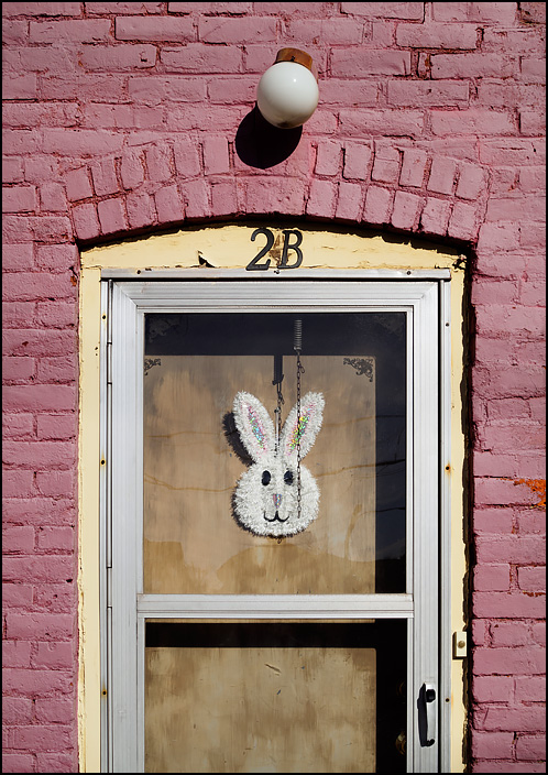 An Easter Bunny decoration on the back door of an old house on Cass Street in Fort Wayne, Indiana. The brick house has been painted pink, and the paint is badly faded.
