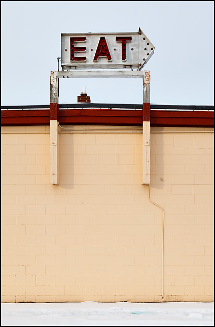 An arrow-shaped sign that says EAT. It is mounted on the top of a diner called the Twentieth Century Restaurant on US-6 near the small town of Milford in rural Elkhart County, Indiana.
