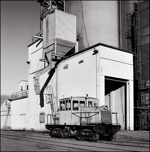 A diesel switching locomotive sits on a railroad siding next to the grain co-op silos and grain elevator in Edgerton, Indiana.