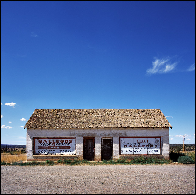 An old whitewashed brick building with boarded up windows covered in signs that say Democrat Adam Gallegos for County Clerk. The building is on route 66 in Tucamcari, New Mexico.