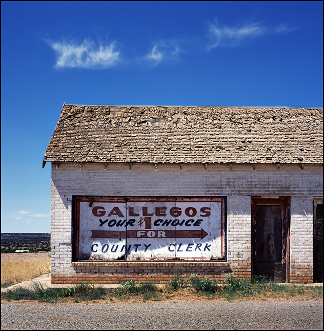 A billboard advertising Adam Gallegos for Quay County Clerk on an abandoned brick building on old Route 66 in Tucamcari, New Mexico.