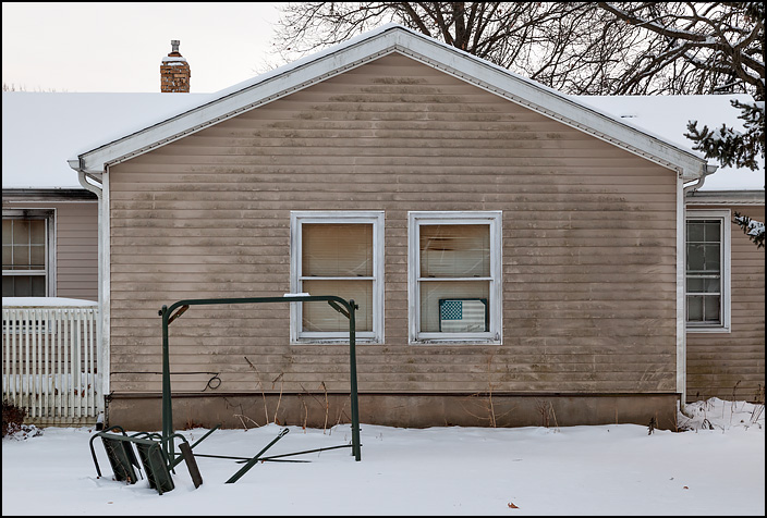 A faded American flag sign with God Bless America written on it hangs in the front window of a house on Christmas Day.