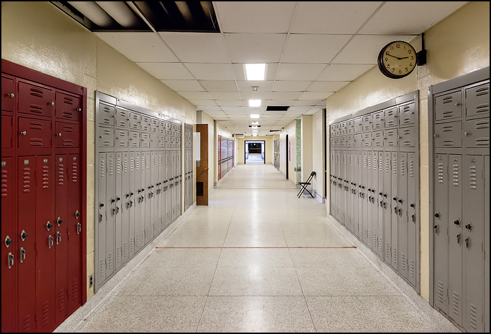 A view of the English Department hall at Elmhurst High School in Fort Wayne, Indiana. The long hallway is lined with red and gray lockers and a lone folding chair sits on one side of the corridor.