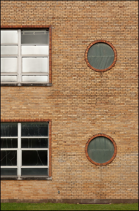 The decorative roundels on the northeast corner of Elmhurst High School in Fort Wayne, Indiana. This part of the building is modernist in style, orange brick with gray round false windows on the corners.