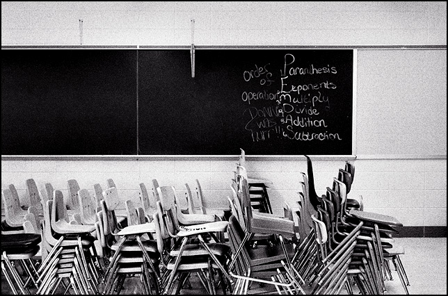 Stacks of chairs sit in front of the blackboard in the abandoned Elmhurst High School in Fort Wayne. A lesson on the mathematical order of operations was left on the blackboard.