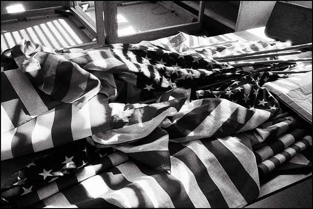 A pile of American flags on a table in the abandoned Elmhurst High School in Fort Wayne, Indiana.