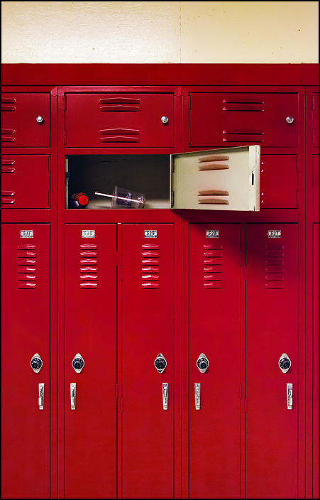 A set of red lockers in the cafeteria hall at Elmhurst High School in Fort Wayne, Indiana. One of the lockers is open, and has an empty McDonalds coffee cup and a plastic drink bottle left behind by a student.