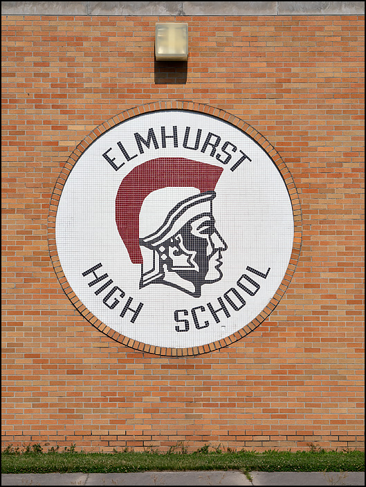 A round glazed tile mosaic of the Elmhurst Trojans logo on the outside of Elmhurst High School in Fort Wayne, Indiana.