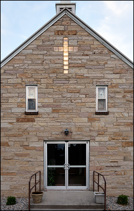 Elmhurst Church of the Nazarene, a small stone church on Sandpoint Road in Fort Wayne, Indiana. Photographed at dusk so that the lighted cross made of glass bricks is visible above the doors.