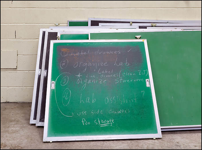 A stack of chalkboards from classrooms at Elmhurst High school lean against a wall during the pre-demolition sale held at the school on January 27, 2018. One of them still has instructions from a science lab assignment written on it.