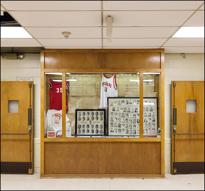 The oak trophy case in the hall outside the main gym at Elmhurst High School in Fort Wayne, Indiana. The case is filled with old photos, newspapers, and other Elmhurst memorabilia loaned by alumni.
