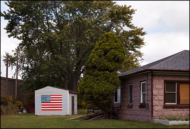 An American Flag painted on the side of a small storage shed behind a house on Elnora Drive in Fort Wayne, Indiana.