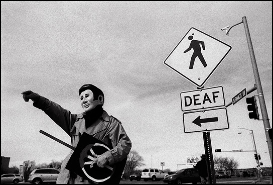 An antiwar demonstrator dressed as Elvis Presley holds a peace sign and points at something in the distance during the weekly demonstration against the Iraq War in Santa Fe, New Mexico.