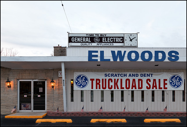 A row of small American flags stand along the front of Elwoods Appliances in Waynedale. A banner says that they are having a scratch and dent sale on General Electric appliances.