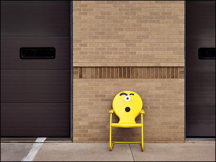 A yellow metal motel chair with a one-eyed emoji on it sits in front of Fire Station 10 at the corner of Crescent and Anthony in Fort Wayne, Indiana.