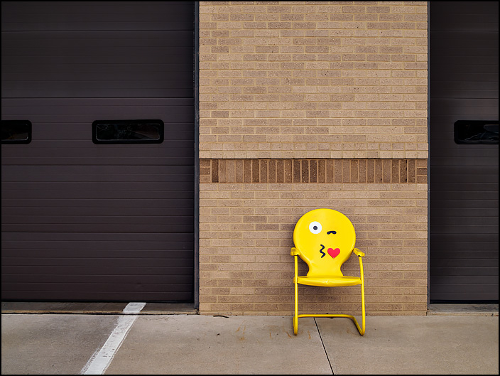 A yellow metal motel chair with a kissing face emoji on it sits in front of Fire Station 10 at the corner of Crescent and Anthony in Fort Wayne, Indiana.