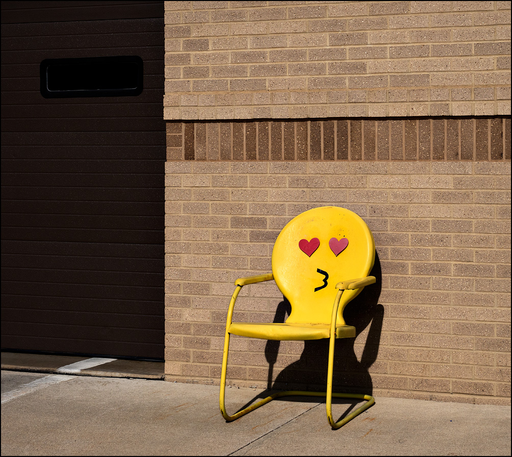 A yellow metal motel chair with a heart-eyes kissing face emoji on it sits in front of Fire Station 10 at the corner of Crescent and Anthony in Fort Wayne, Indiana.