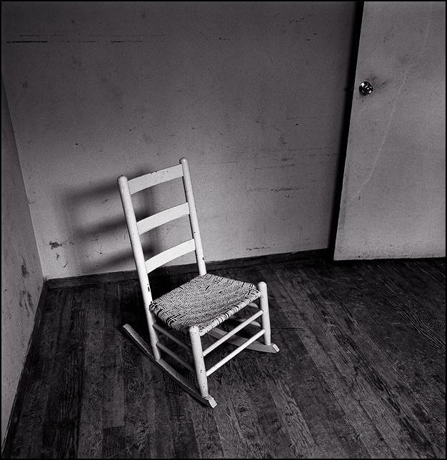 An old beat-up wooden rocking chair sits alone in an empty room in my grandpas vacant house.