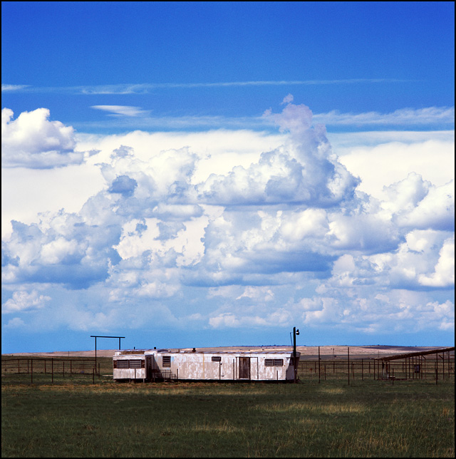 Two old mobile homes in a grassy field under dramatic clouds near the livestock pens on a ranch on US-285 near Encino, New Mexico.