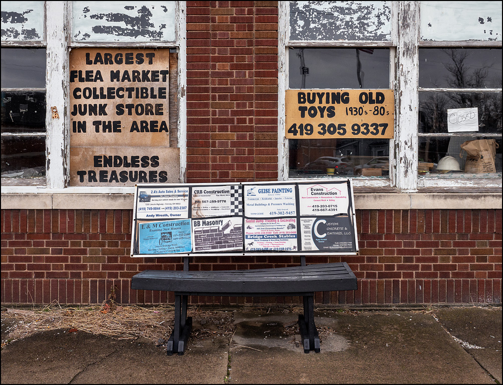 A park bench covered in advertising sits in front of the Van Wert Variety Store in the small town of Van Wert, Ohio. The store is an old brick warehouse whose windows are covered in signs that say Endless Treasures, Buying Old Toys, Largest flea market collectible junk store in the area.