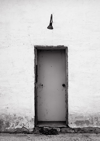 An old light hangs above a door on the side of an abandoned adobe building in Estancia, New Mexico.