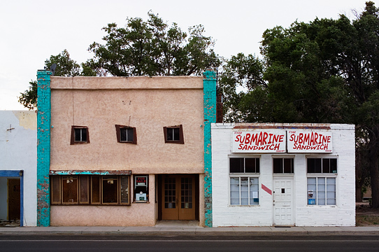 An abandoned theater and an abandoned sub shop sit next to each other on the main street of Estancia, New Mexico.