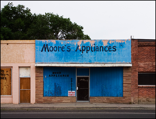 The boarded up storefront of Moore's Appliances in Estancia, New Mexico. Other abandoned stores sit on both sides of it.