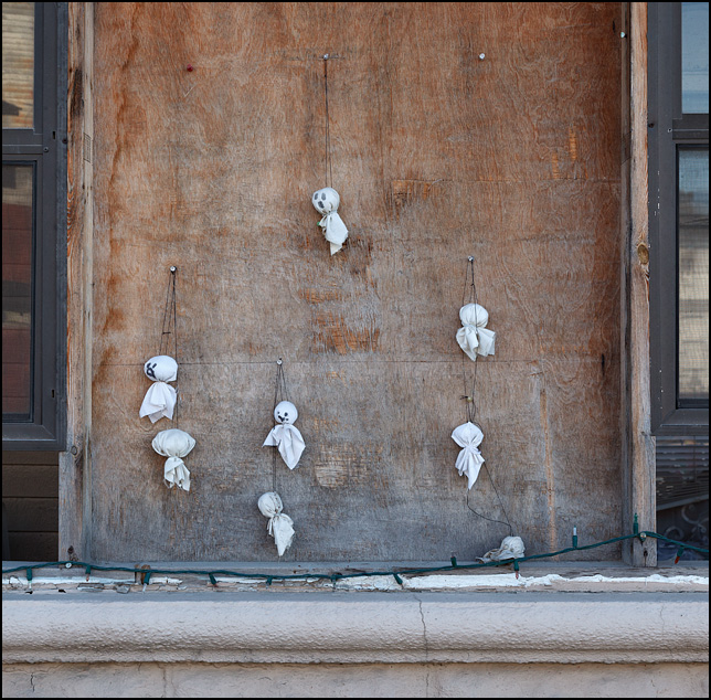 Small handmade ghosts made of white fabric hang on the boarded-up porch window of an old house in the small town of Etna Green, Indiana. The house was decorated for Halloween.