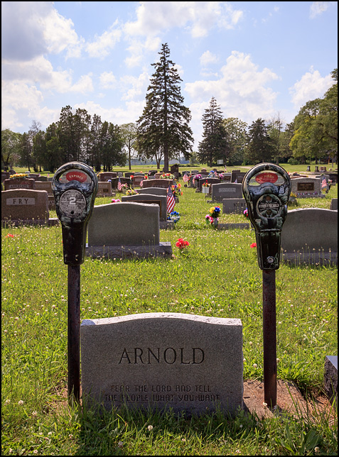 Two expired parking meters mounted on the tombstone of Archie Arnold at the Scipio Cemetery on State Road 37 in Allen County, Indiana.
