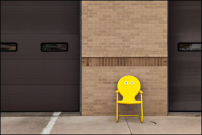 A yellow metal motel chair with an emoji face that has eyes and no mouth painted on it sits in front of Fire Station 10 at the corner of Crescent and Anthony in Fort Wayne, Indiana.