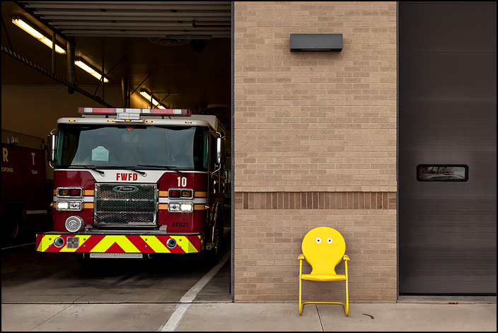 A yellow metal motel chair with eyes painted on it sits in front of Fire Station 10 at the corner of Crescent and Anthony in Fort Wayne, Indiana. One of the garage doors is open and a fire truck is about to drive out.