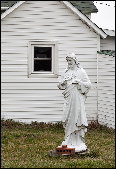 A life sized statue of Jesus Christ stands next to a white farmhouse on Johnson Road in rural Allen County, Indiana.