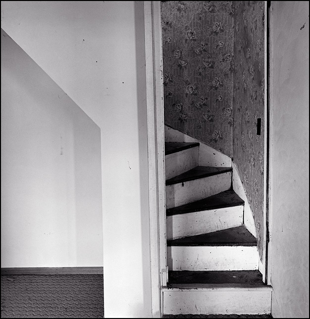 The stairs in an abandoned farmhouse go up a few steps before turning to go the rest of the way up to the second floor.