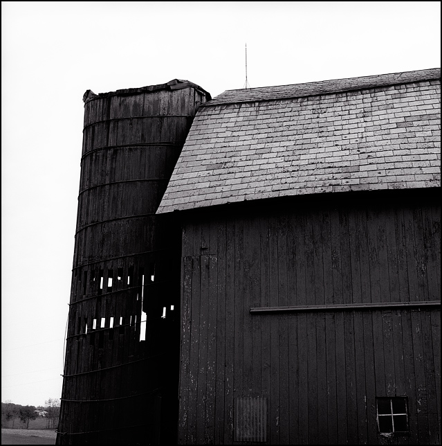 An old wooden silo and rundown barn with a slate roof and a lightening rod at an abandoned farm on Feighner Road in southwest Allen County, Indiana.