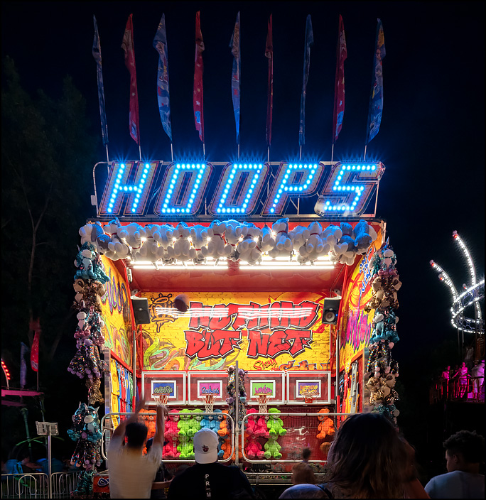 A man shoots hoops at a basketball game at the 2019 Three Rivers Festival in Fort Wayne, Indiana. Stuffed animal prizes hang all around the brightly lit game at night.